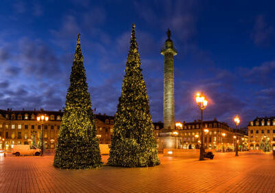 Panoramic view of Place Vendome with Christmas trees and holiday decorations at dusk. In the center, the Vendome column with the statue of Napoleon. 1st Arrondissement, Paris, France